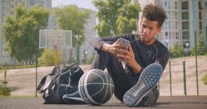 使用电话的年轻坚强的非裔美国人的男性篮球运动员特写镜头画象和看照相机坐 股票录像