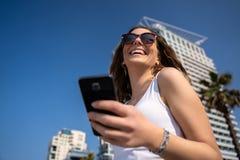 使用电话的年轻女人 城市地平线在背景中 免版税库存照片