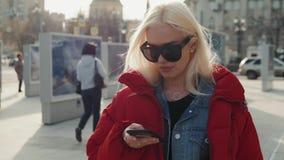 使用电话的年轻愉快的十几岁的女孩和获得乐趣在春天公园 白肤金发的愉快的式样妇女画象学生下来 股票录像