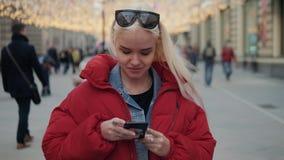 使用电话的年轻愉快的十几岁的女孩和获得乐趣在春天公园 白肤金发的愉快的式样妇女画象学生下来 股票视频