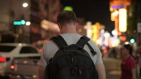 使用电话的年轻旅游人背包徒步旅行者背面图在唐人街在晚上 影视素材