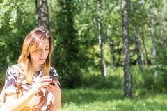 使用电话的年轻红头发人妇女户外在一个晴天 Po 免版税库存照片