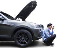 使用电话的恼怒的人乘残破的汽车 库存图片