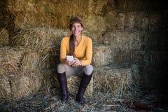使用电话的愉快的女性骑师,当坐干草在槽枥时 免版税库存照片
