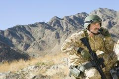 使用电话的战士,当拿着步枪反对山时 免版税库存照片