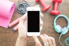 使用电话的手染黑在顶视图的屏幕与健身equipmen 库存图片