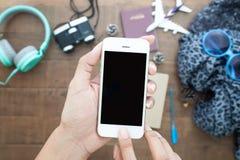 使用电话的手染黑在顶视图的屏幕与护照, binocu 图库摄影