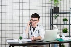 使用电话的男性医生,当研究计算机在桌在诊所时 免版税库存图片