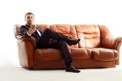 使用电话的疲乏的商人坐长沙发 免版税库存图片