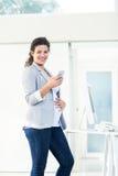 使用电话的确信的怀孕的女实业家画象  免版税库存照片