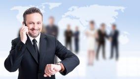 使用电话的繁忙的商人和检查时间 免版税库存照片