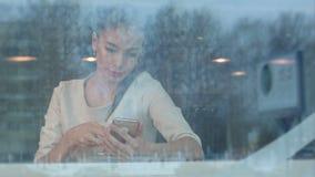 使用电话的美丽的女孩,当喝咖啡在通过窗口时被观看的咖啡馆 影视素材