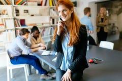 使用电话的美丽的女实业家 免版税库存图片