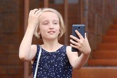 使用电话的美丽的白肤金发的青春期前的女孩,做照片一台前面照相机,采取与手机的一张自画象 免版税图库摄影