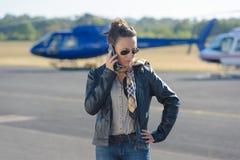 使用电话的美丽的飞行员在背景直升机 免版税库存图片