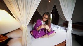 使用电话的美女在处理有流动应用程序的床聪明的被连接的家 股票视频