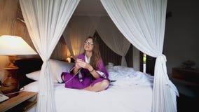 使用电话的美女在处理有流动应用程序的床聪明的被连接的家 影视素材