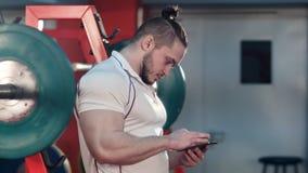 使用电话的肌肉人在锻炼之间的健身房 免版税库存照片
