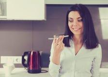 使用电话的语音识别的妇女的画象站立在房子的厨房 库存照片