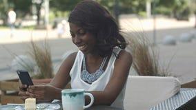 使用电话的非裔美国人的妇女,当坐在外部咖啡馆时 库存照片