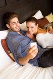 使用电话的年轻夫妇在一个亚洲旅馆客房 库存图片