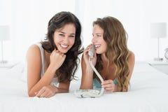使用电话的轻松的年轻女性朋友在床 免版税库存照片