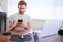 使用电话的年轻白种人人,当坐在他的书桌时 免版税库存照片