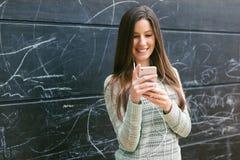使用电话的年轻美丽的妇女在前面黑板墙壁 免版税库存图片