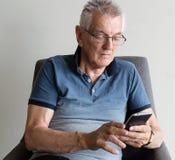 使用电话的更老的人 免版税库存照片