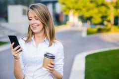 使用电话的年轻聪明的职业妇女读书 女性女实业家读书新闻或短信的sms在智能手机 免版税库存照片