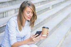 使用电话的年轻聪明的职业妇女读书 女性busin 免版税库存图片