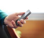使用电话移动电话的人户内 免版税图库摄影