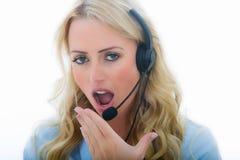 使用电话耳机的可爱的疲乏或乏味年轻女商人 库存图片