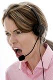 使用电话耳机的恼怒的可爱的年轻女商人 图库摄影