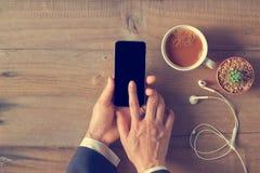 使用电话黑色屏幕的手在木背景 免版税库存照片