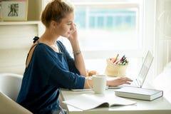 使用电话app的愉快的妇女在舒适家庭办公室 免版税库存图片