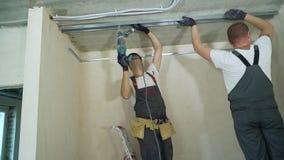 使用电钻聚集的金属干式墙外形的男性建造者在建造场所户内 股票录像