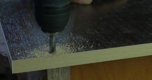 使用电钻的木匠杂物工做孔在木制品车间桌上的板条 钻子做一个孔 股票视频