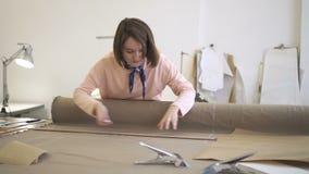 使用白垩和统治者,年轻女性时装设计师在纺织品工作,做标号,站立在缝合的桌上 股票视频