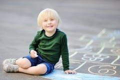 使用白垩的逗人喜爱的小男孩图画跳房子在沥青 免版税库存图片