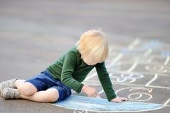 使用白垩的逗人喜爱的小男孩图画跳房子在沥青 免版税库存照片