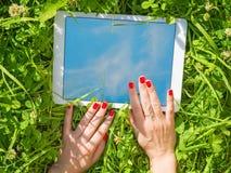 使用白色片剂个人计算机的女性手在绿草 库存照片