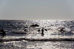使用的人剪影,游泳在波浪在拔摩岛海岛,夏时的希腊 库存照片