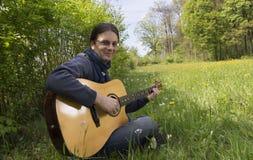 使用的吉他弹奏者户外 库存照片