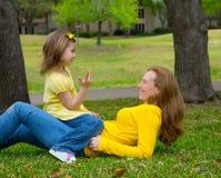 使用的女儿和的母亲计数说谎在草坪 免版税库存照片