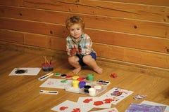 使用的孩子学会和 男孩在木地板上的画家绘画 库存照片