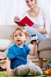 使用的孩子,当母亲读时 库存图片