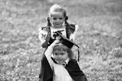 使用的孩子-愉快的比赛 打扮毕业帽子和长袍的逗人喜爱的女孩小男孩 库存照片