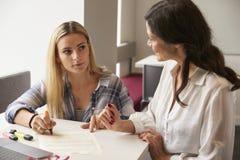使用的家庭教师学会援助帮助有阅读困难的学生 库存照片