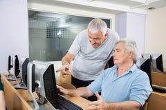 使用的计算机老人帮助的同学 免版税库存照片